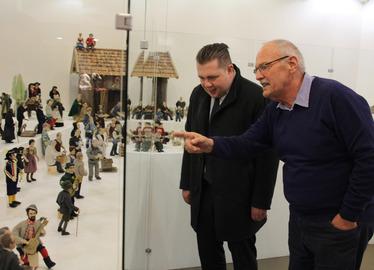 -Krippenreferent Heinz Häusler (re.), wie er Landrat Michael Adam die Figuren erklärt. Foto: Langer/Landkreis Regen