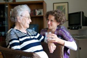 Seniorin wird ein Glas Wasser gereicht
