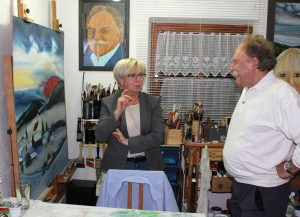 Derzeit arbeitet der Künstler an einem Schönau-Bild. Landrätin Rita Röhrl ließ sich von Hans Jürgen Orzechowski seine Arbeitsweise erklären. Foto: Langer/Landkreis Regen