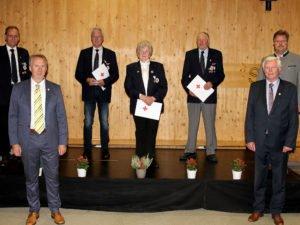 Das BRK nutzte die Gelegenheit um drei Ehrungen vorzunehmen. Maria Andreas aus Bodenmais wurde für ihren 60-jährigen Einsatz bei der Bereitschaft Bodenmais mit der DRK-Ehrennadel ausgezeichnet. Für 50-jährige Treue und Unterstützung wurden Edwin (3.v.li.) und Karl Heinz Schedlbauer (5.v.li.) aus Viechtach geehrt. Auf der Bühne gratulierten BRK-Kreisgeschäftsführer Günther Aulinger (li.), stellvertretende Landrat Helmut Plenk (2.v.li.), der stellvertretene Kreisvorsitzende des BKR Walter Fritz und der Bodenmaiser Bürgermeister Joli Haller (re.). Foto: Langer