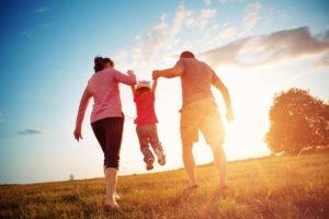Eltern heben Kind auf der Wiese spielend in die Luft. Foto: © Adobe Stock/candy1812