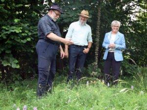 Karl Reitmeier zeigte Klaus Eder und Landrätin Rita Röhrl seinen Garten. Dabei präsentiere er mit dem gefleckten Knabenkraut eine Besonderheit in der Blühwiese. Foto: Langer/Landkreis Regen