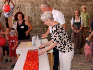 Mit dem Jugendamtsleiter Martin Hackl als Assistenten schnitt die Landrätin den Geburtstagskuchen an und überreichte Kindern die ersten Stücke. Foto: Langer/Landkreis Regen
