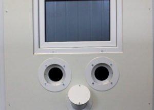 Der Tester steht hinter der Glasscheibe und ist so vor Ansteckung geschützt. Foto: Langer/Landkreis Regen